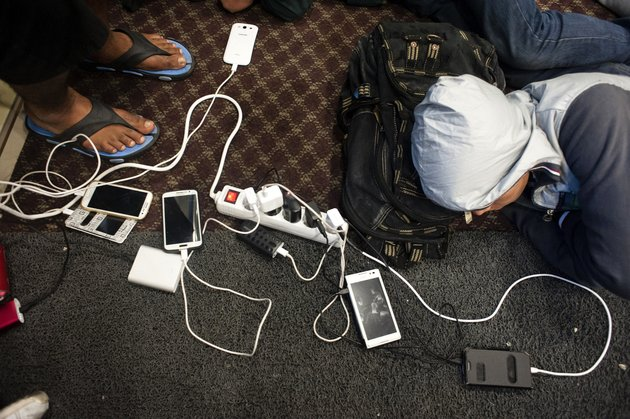 Refugees and migrants charge their mobile phones as they rest on the 'Ariadni' ferry after leaving the Greek island of Lesbos for the port of Piraeus in Athens, on September 28, 2015. UN Secretary-General Ban Ki-moon welcomed the European Union's decision to inject $1 billion to help countries overwhelmed by Syrian refugees, but said more must be done to relocate migrants. AFP PHOTO / IAKOVOS HATZISTAVROU        (Photo credit should read IAKOVOS HATZISTAVROU/AFP/Getty Images)